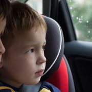 Young brothers looking out car window